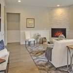 Luxury living room features corner stone fireplace